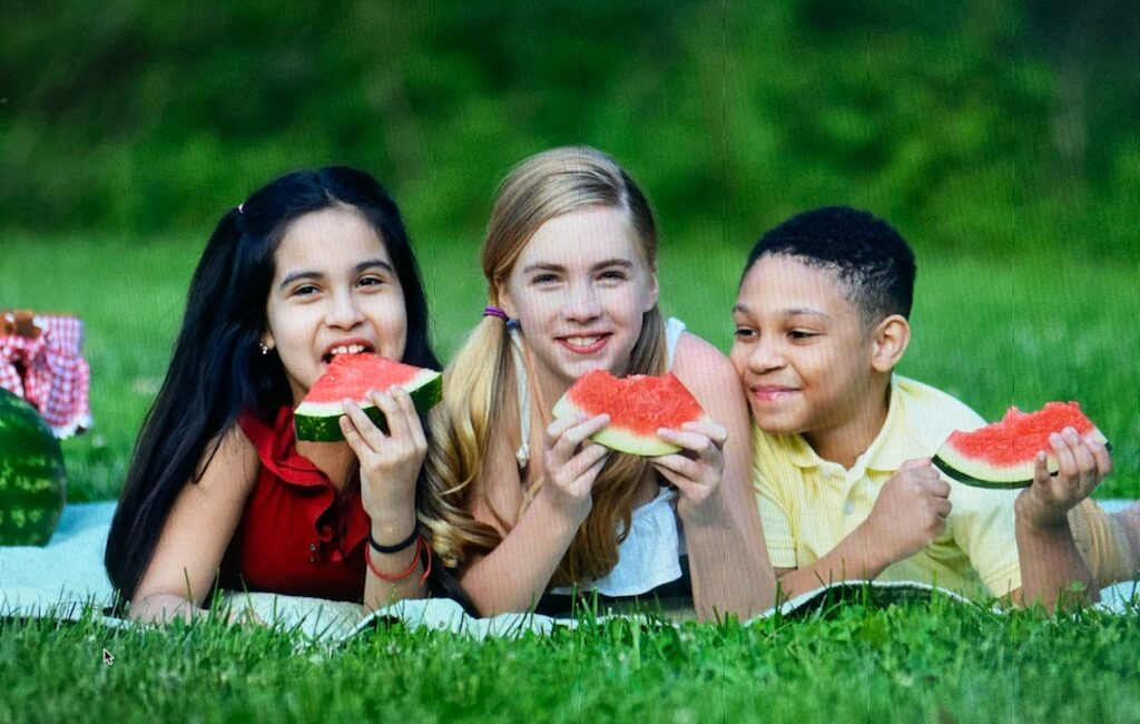 kids on a blanket eating watermelon
